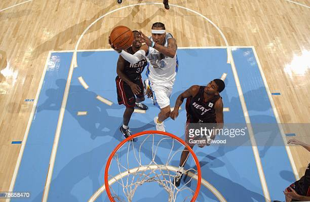 Allen Iverson of the Denver Nuggets drives to the basket for a layup between Ricky Davis and Dorell Wright of the Miami Heat during the game at Pepsi...