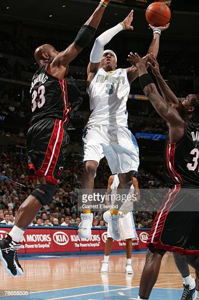 Allen Iverson of the Denver Nuggets goes up for a shot against Alonzo Mourning and Ricky Davis of the Miami Heat during the game at Pepsi Center on...
