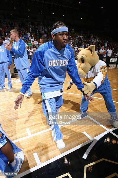 Allen Iverson of the Denver Nuggets high fives team mascot Rocky as he enters the court during player introductions prior to a preseason game against...