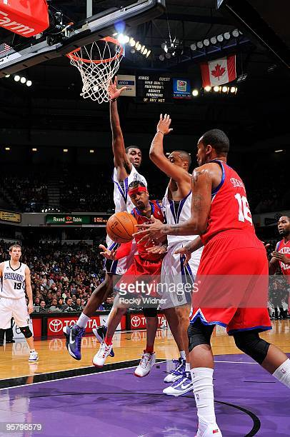 Allen Iverson of the Philadelphia 76ers moves the ball against Donte Greene and Kenny Thomas of the Sacramento Kings during the game on December 30...