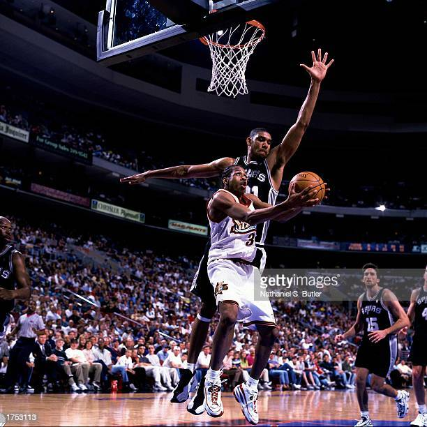 Allen Iverson of the Philadelphia 76ers shoots a reverse layup against Tim Duncan of the San Antonio Spurs at the First Union Center in the 1998...