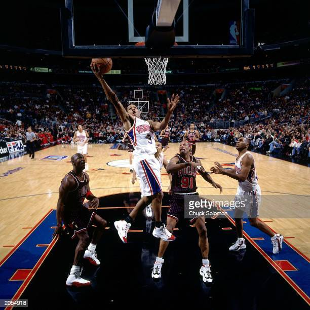Allen Iverson of the Philadelphia 76ers shoots against Michael Jordan and Dennis Rodman of the Chicago Bulls during the NBA game at the Spectrum on...