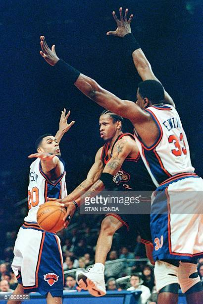 Allen Iverson of the Philadelphia SeventySixers looks to pass to a teammate and jumps through the outstretched hands of Allan Houston and Patrick...