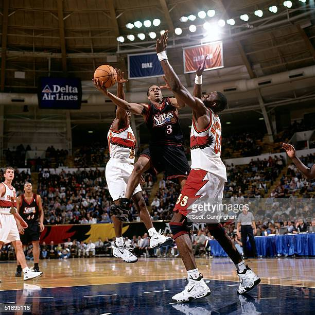 Allen Iverson of the Philadelphia Sixers drives to the basket against Dikembe Mutombo of the Atlanta Hawks during a NBA game at the the Omni in...