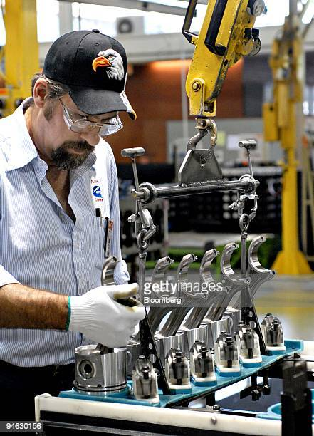 Allen Robinson of North Vernon Indiana drops pistons into a template before placing them into an engine block at the Cummins Inc engine plant in...