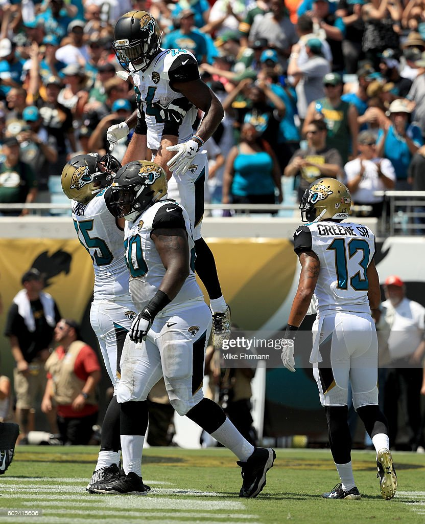 Allen Robinson #15 of the Jacksonville Jaguars lifts T.J. Yeldon #24 while Rashad Greene Sr #13 looks on as they celebrate Yeldon's touchdown during the game against the Green Bay Packers at EverBank Field on September 11, 2016 in Jacksonville, Florida.