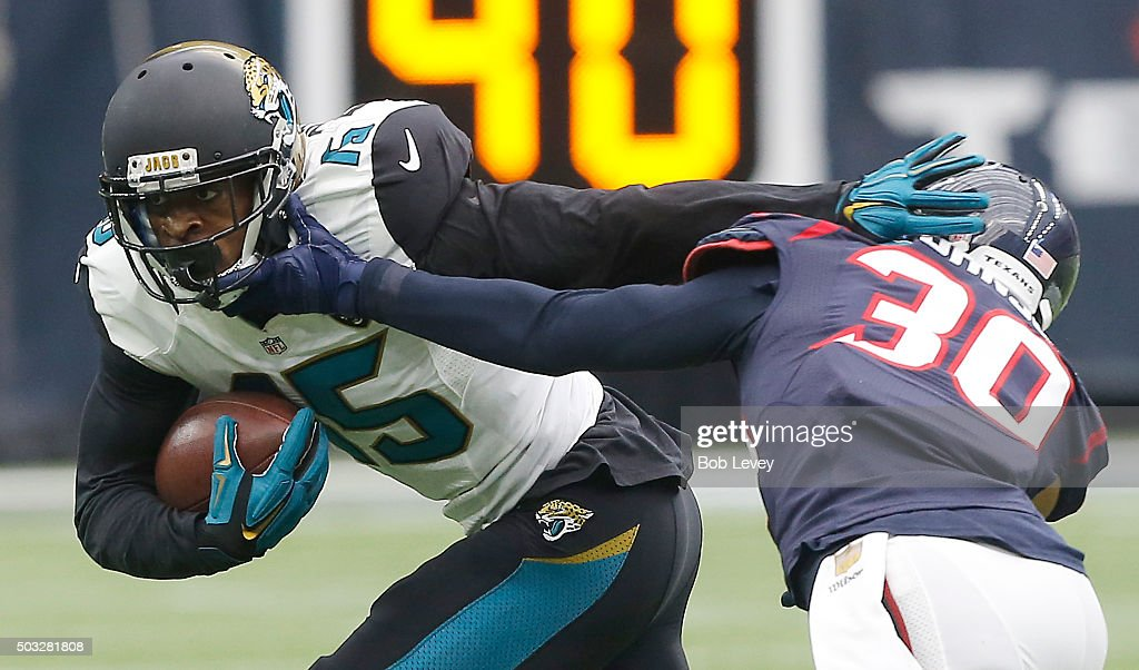 Allen Robinson of the Jacksonville Jaguars stiff arms Kevin Johnson of the Houston Texans in the first quarter on January 3 2016 at NRG Stadium in...