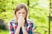 Woman with allergy symptom blowing nose