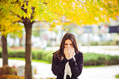 Young girl in autumn park blowing nose. Standing in park in warm clothing.
