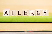 Allergy word built with letter cubes on green book