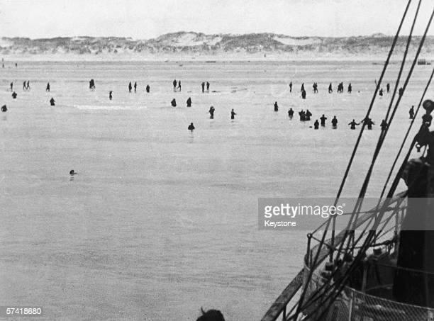 Allied troops wade out to an evacuation vessel moored off Dunkirk during World War II 1940