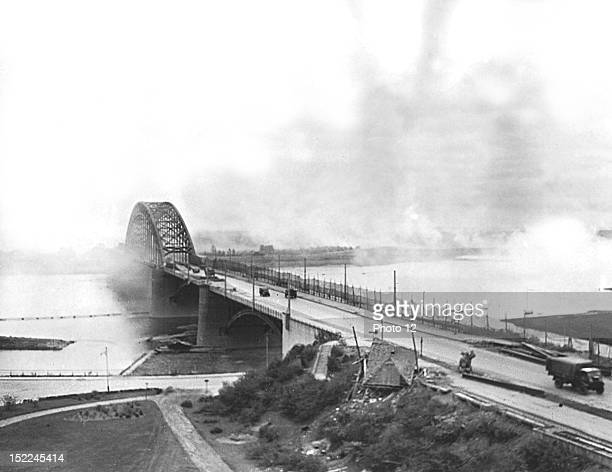 Allied trucks carrying munitions and supplies to troops on the Western front in Holland cross the bridge over the Waal river at Nijmegen under German...