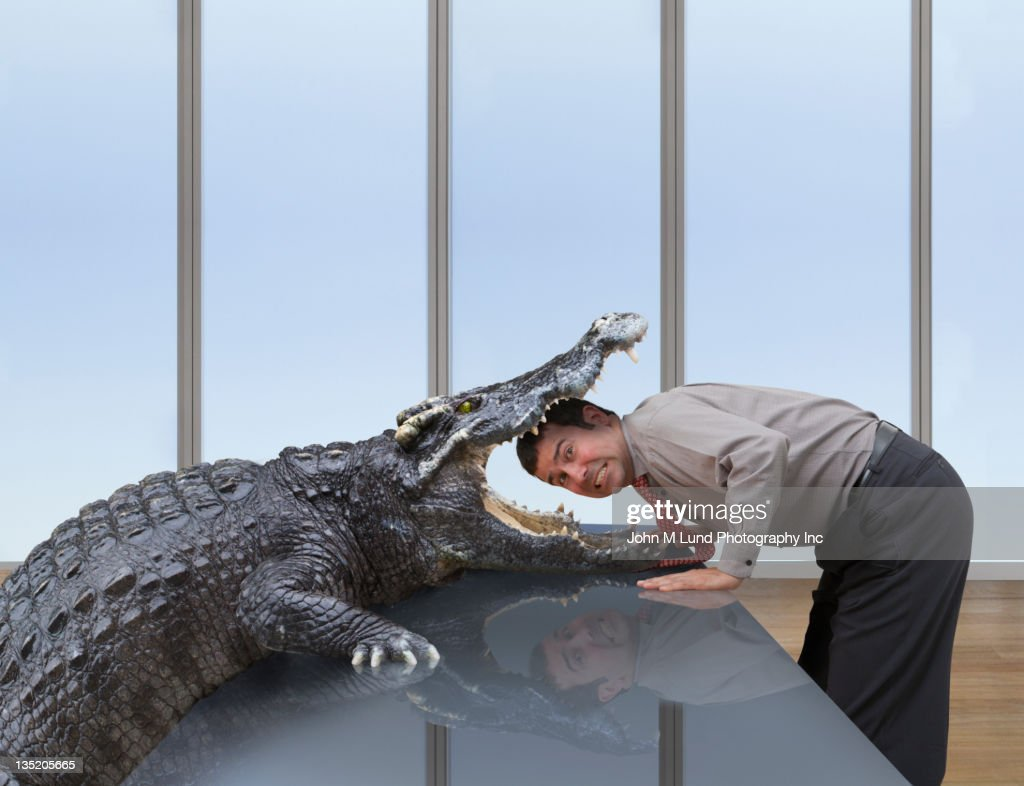 Alligator eating Caucasian businessman
