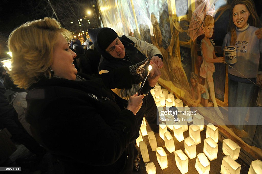 Allison Halwick and Bill Fairer light candles for luminaries at a candlelight vigil marking one year since Joe Paterno's death at the Inspiration Mural in State College, Pennsylvania, on Tuesday, January 22, 2013.
