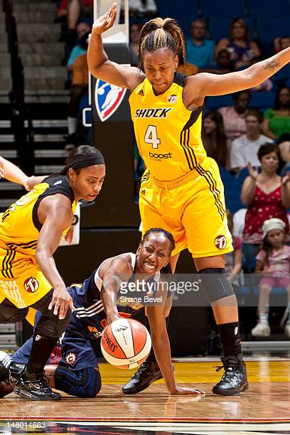 Allison Hightower of the Connecticut Sun loses control of the ball under pressure from Ivory Latta and Amber Holt of the Tulsa Shock during the WNBA...