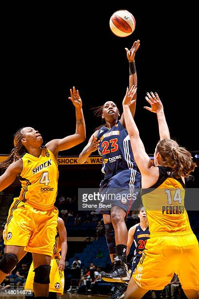 Allison Hightower of the Connecticut Sun shoots over Kayla Peterson and Amber Holt of the Tulsa Shock during the WNBA game on July 6 2012 at the BOK...