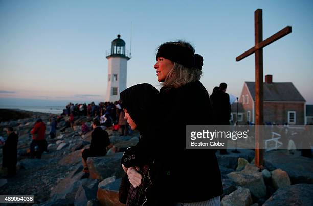 Allison Monger of Scituate Mass embraces her son William as they watch the sun come up during sunrise service at the Old Scituate Lighthouse in...
