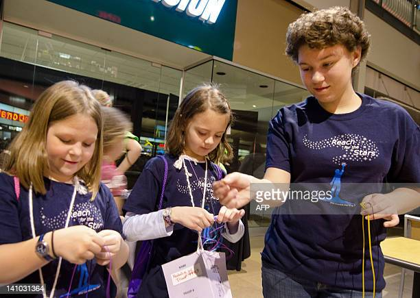 Allison Seitz helps younger fellow members of the Girl Scouts of Central Maryland work towards an arts and crafts badge at a shoppingmall sleepover...