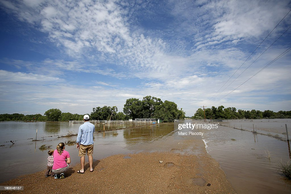 Allison Wold of Denver, Colorado and her nephew, Jack Wold, take in a flooded ranch home with John Brinckerhoff, also of Denver after heavy flooding September 14, 2013 near Dearfield, Colorado. They were trying to cross County Road 87 to get to some family property but couldn't because of the flooding. Heavy rains for the better part of week fueled widespread flooding in numerous Colorado towns. he historic flooding forced thousands to evacuate the area and more rain is predicted through the weekend.