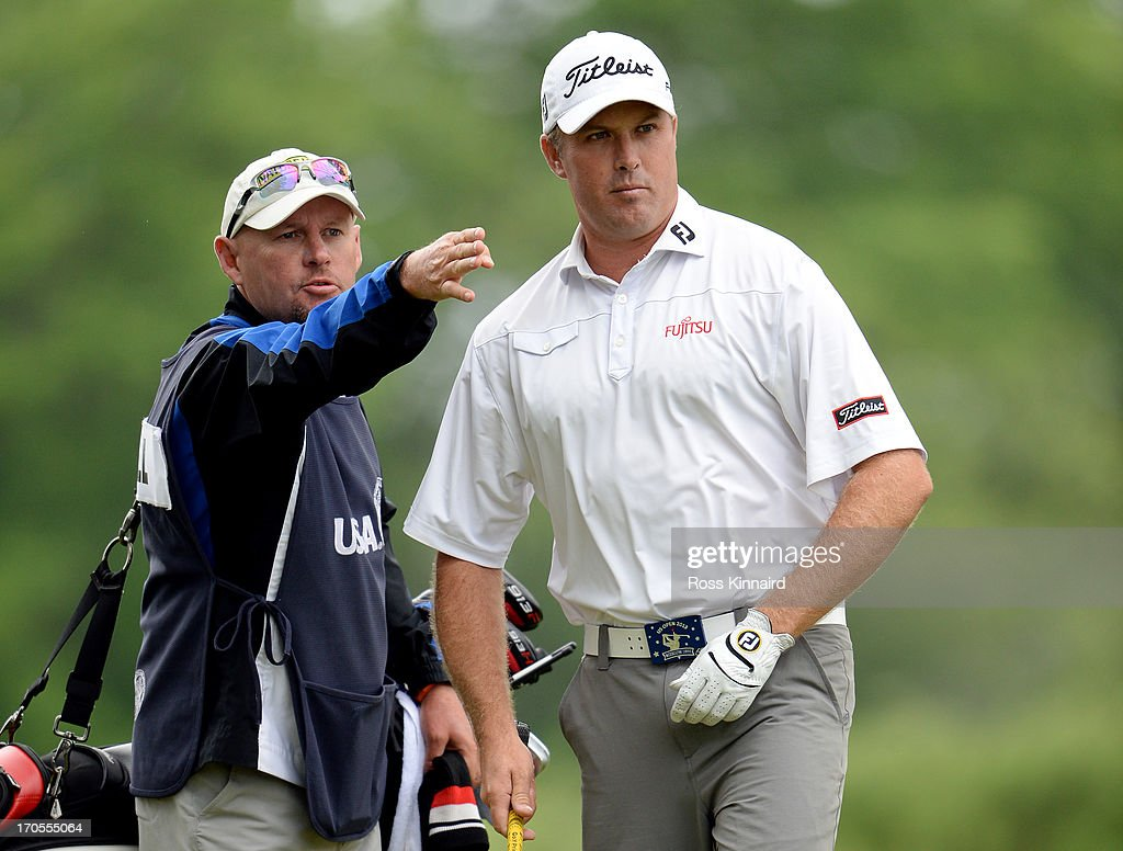 Allistair Presnell of Australia talks with his caddie on the fifth hole during a continuation of Round One of the 113th U.S. Open at Merion Golf Club on June 14, 2013 in Ardmore, Pennsylvania.