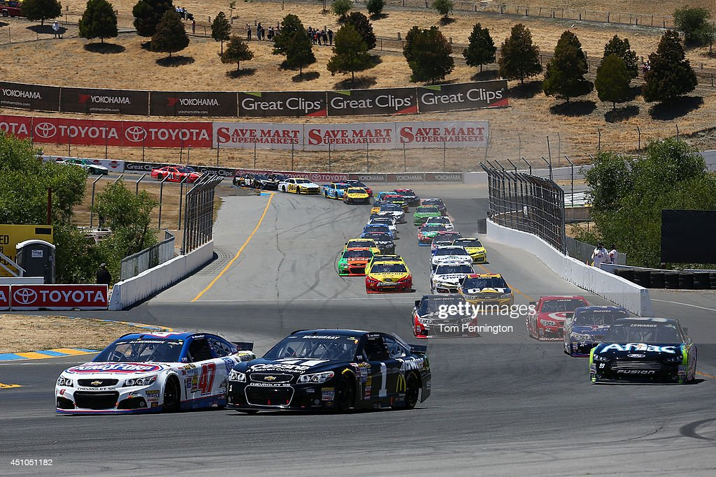 Allmendinger driver of the Clorox/Kingsford Chevrolet and Jamie McMurray driver of the Cessna Chevrolet race through turn seven on the first lap of...