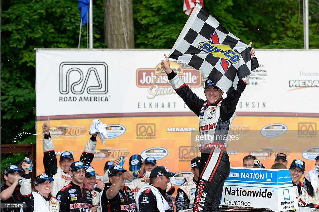 AJ Allmendinger, driver of the #22 Discount Tire Ford, celebrates in Victory Lane after winning the NASCAR Nationwide Series Johnsonville Sausage 200 Presented by Menards at Road America on June 22, 2013 in Elkhart Lake, Wisconsin.