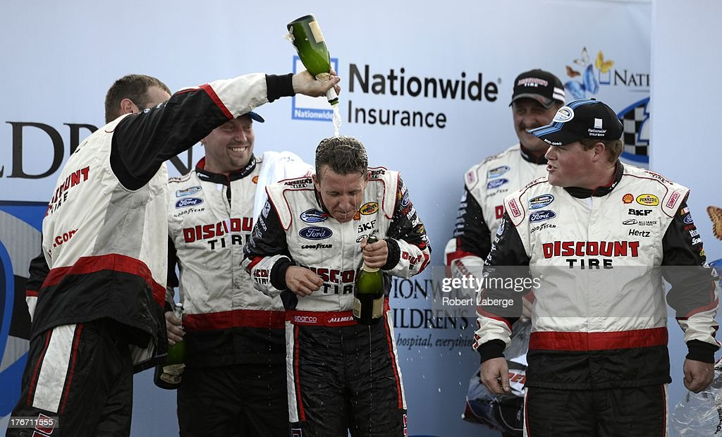 AJ Allmendinger, driver of the #22 Discount Tire Ford, celebrates with his crew in Victory Lane after winning the NASCAR Nationwide Series Children's Hospital 200 at the Mid-Ohio Sports Car Course on August 17, 2013 in Lexington, Ohio.