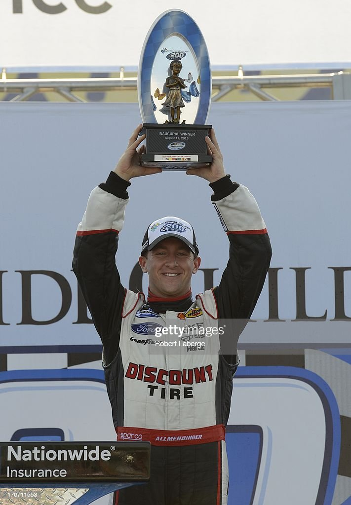 AJ Allmendinger, driver of the #22 Discount Tire Ford, lifts the winner's trophy after winning the NASCAR Nationwide Series Children's Hospital 200 at the Mid-Ohio Sports Car Course on August 17, 2013 in Lexington, Ohio.