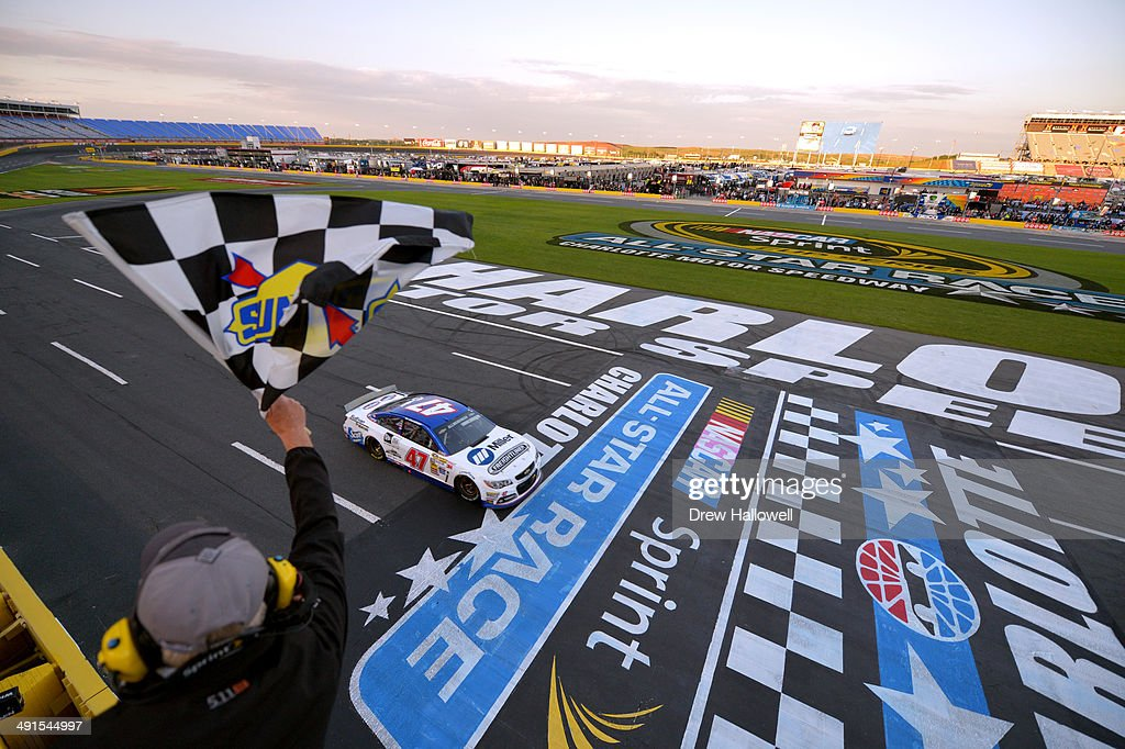 AJ Allmendinger, driver of the #47 Freightliner-Miller Welders Chevrolet, takes the checkered flag as he crosses the finish line to win the NASCAR Sprint Cup Series Sprint Showdown at Charlotte Motor Speedway on May 16, 2014 in Charlotte, North Carolina.