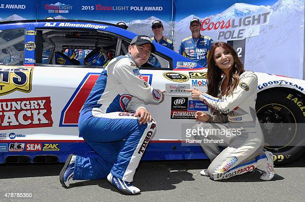 Allmendinger driver of the Kingsford Charcoal Chevrolet poses with Miss Coors Light Amanda Mertz and the Coors Light Pole Award decal after...