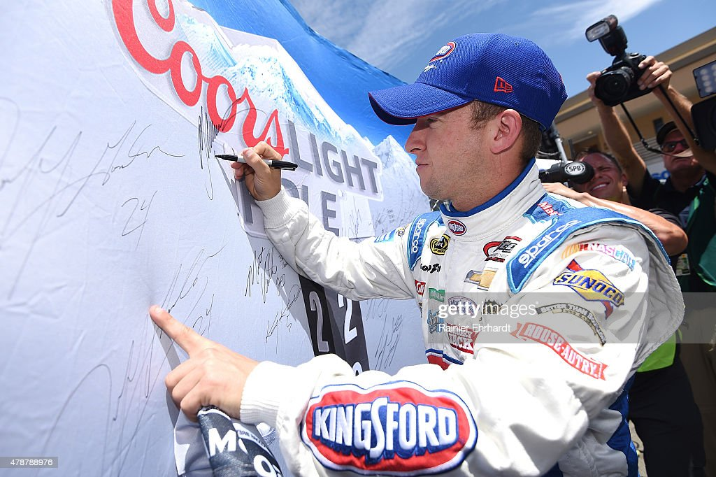 AJ Allmendinger, driver of the #47 Kingsford Charcoal Chevrolet, signs the Coors Light Pole Award board after qualifying for pole position for the NASCAR Sprint Cup Series Toyota/Save Mart 350 at Sonoma Raceway on June 27, 2015 in Sonoma, California.