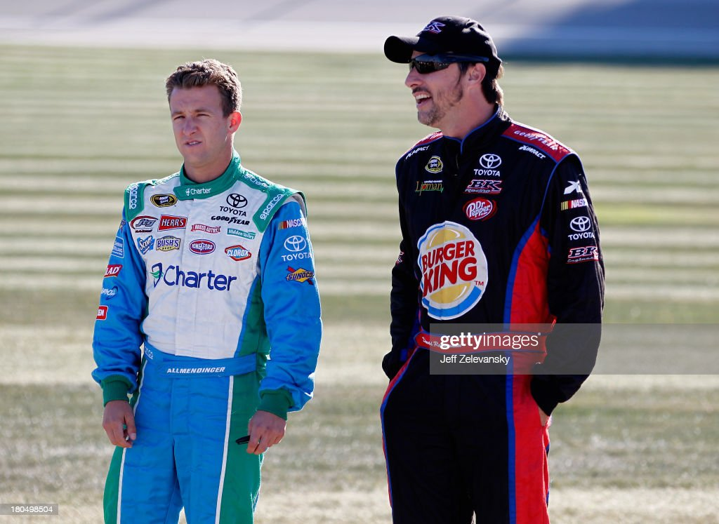 AJ Allmendinger, driver of the #47 Kingsford Charcoal Toyota, speaks with David Reutimann, driver of the #83 Burger King/Dr Pepper Toyota, during qualifying for the NASCAR Sprint Cup Series Geico 400 at Chicagoland Speedway on September 13, 2013 in Joliet, Illinois.