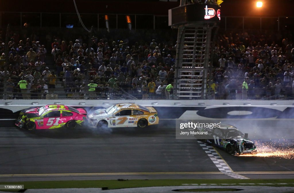 AJ Allmendinger, driver of the #51 Phoenix Construction Chevrolet, Dave Blaney, driver of the #7 Florida Lottery Chevrolet, and Denny Hamlin, driver of the #11 FedEx Ground Toyota, are involved in an incident during the NASCAR Sprint Cup Series Coke Zero 400 at Daytona International Speedway on July 6, 2013 in Daytona Beach, Florida.