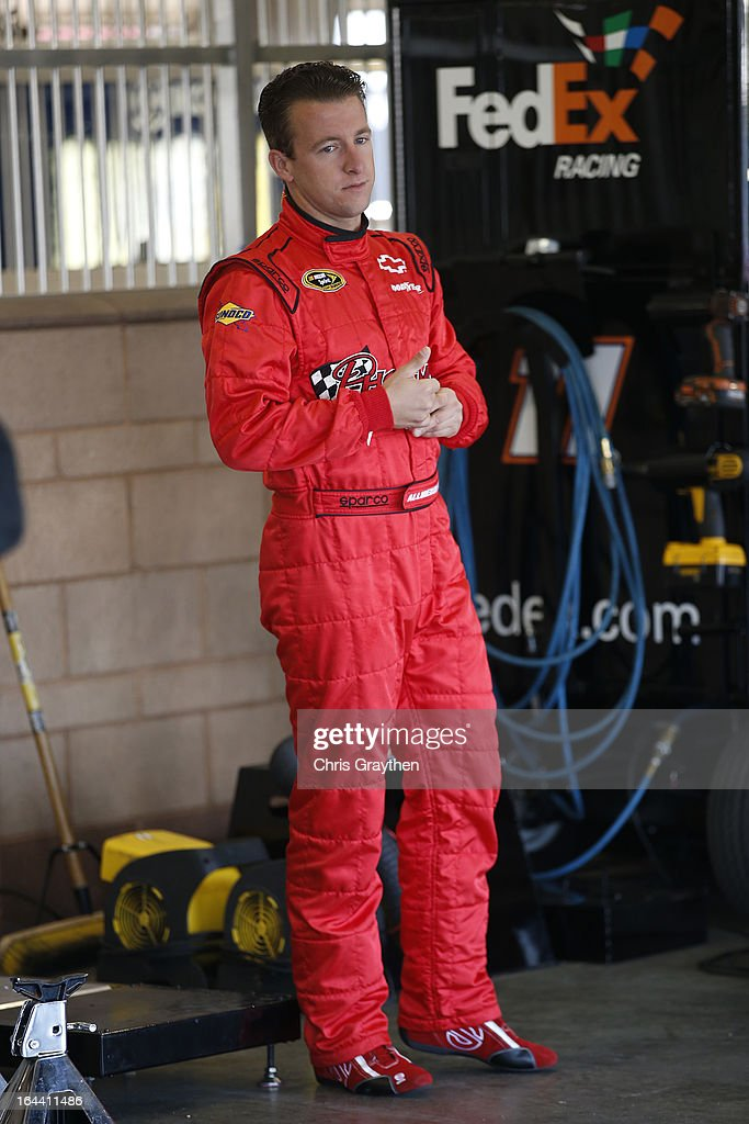 AJ Allmendinger, driver of the #51 Phoenix Construction Chevrolet, stands in the garage area during practice for the NASCAR Sprint Cup Series Auto Club 400 at Auto Club Speedway on March 23, 2013 in Fontana, California.