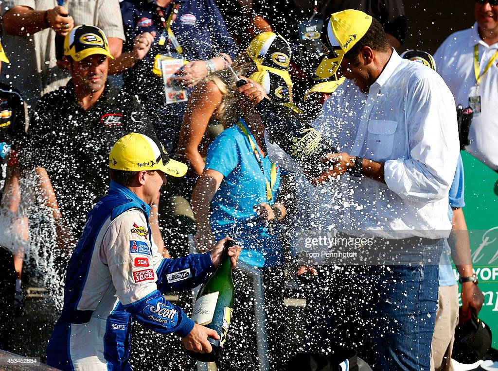 Allmendinger driver of the Scott Products Chevrolet celebrates in Victory Lane with champagne after winning the NASCAR Sprint Cup Series CheezIt 355...