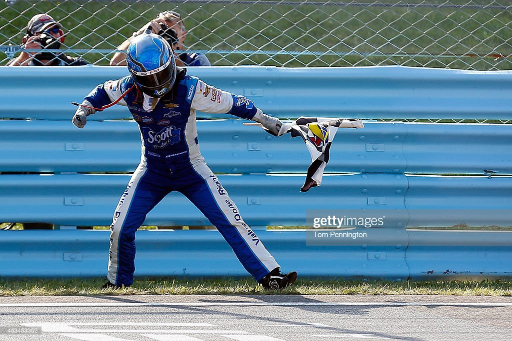 Allmendinger driver of the Scott Products Chevrolet celebrates with the checkered flag after winning the NASCAR Sprint Cup Series CheezIt 355 at...