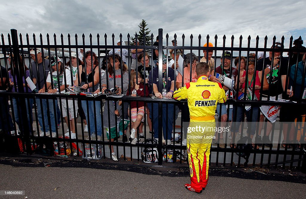 AJ Allmendinger, driver of the #22 Shell/Pennzoil Dodge, signs autographs during qualifying for the NASCAR Sprint Cup Series Pocono 400 presented by #NASCAR at Pocono Raceway on June 9, 2012 in Long Pond, Pennsylvania.