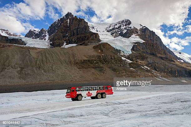 Allwheeldrive three axle snow coach with tourists on the retreating Athabasca Glacier part of the Columbia Icefield in the Canadian Rockies Jasper...