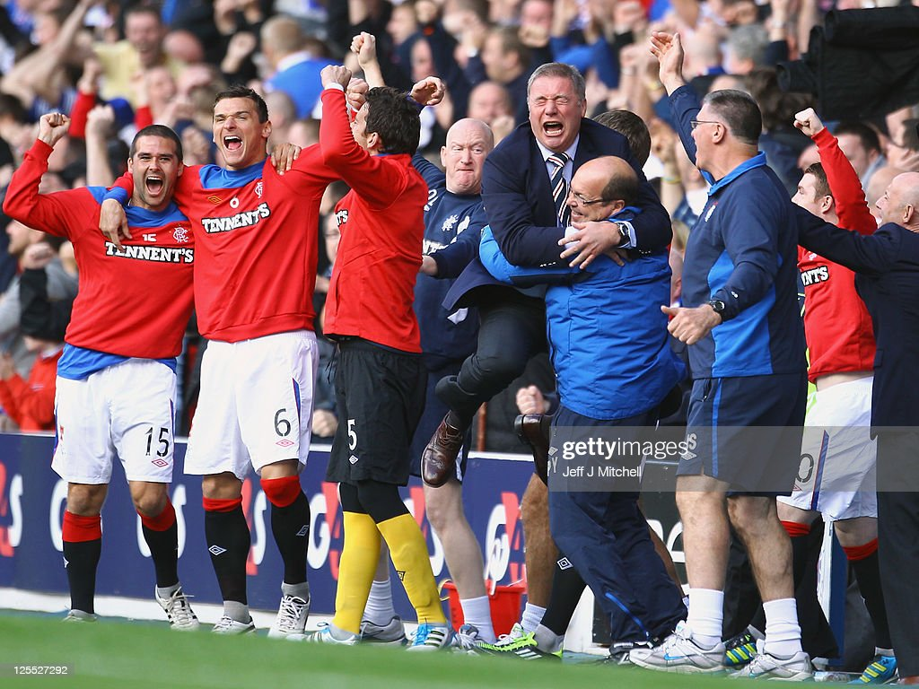 Ally McCoist coach of Rangers tackles celebrates his teams equaliser during the Clydesdale Bank Premier League match between Rangers and Celtic at Ibrox Stadium on September 18, 2011 in Glasgow, Scotland.