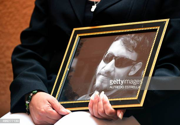 Alma Espinosa holds a portrait of her brother Mexican photojournalist Ruben Espinosa during an interview with AFP in Mexico City on November 27 2015...