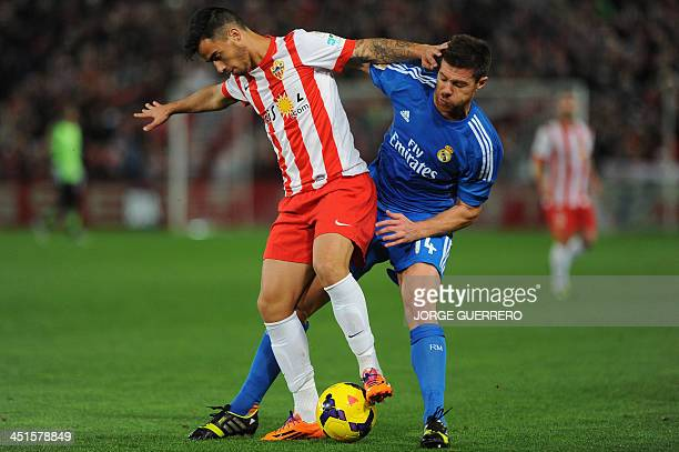 Almeria's midfielder Suso vies with Real Madrid's midfielder Xabi Alonso during the Spanish league football match UD Almeria vs Real Madrid CF at the...