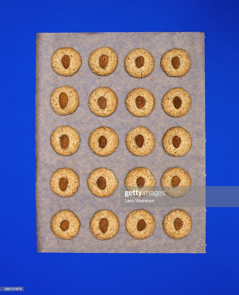 Almond biscuits on baking paper against blue background : Stock Photo