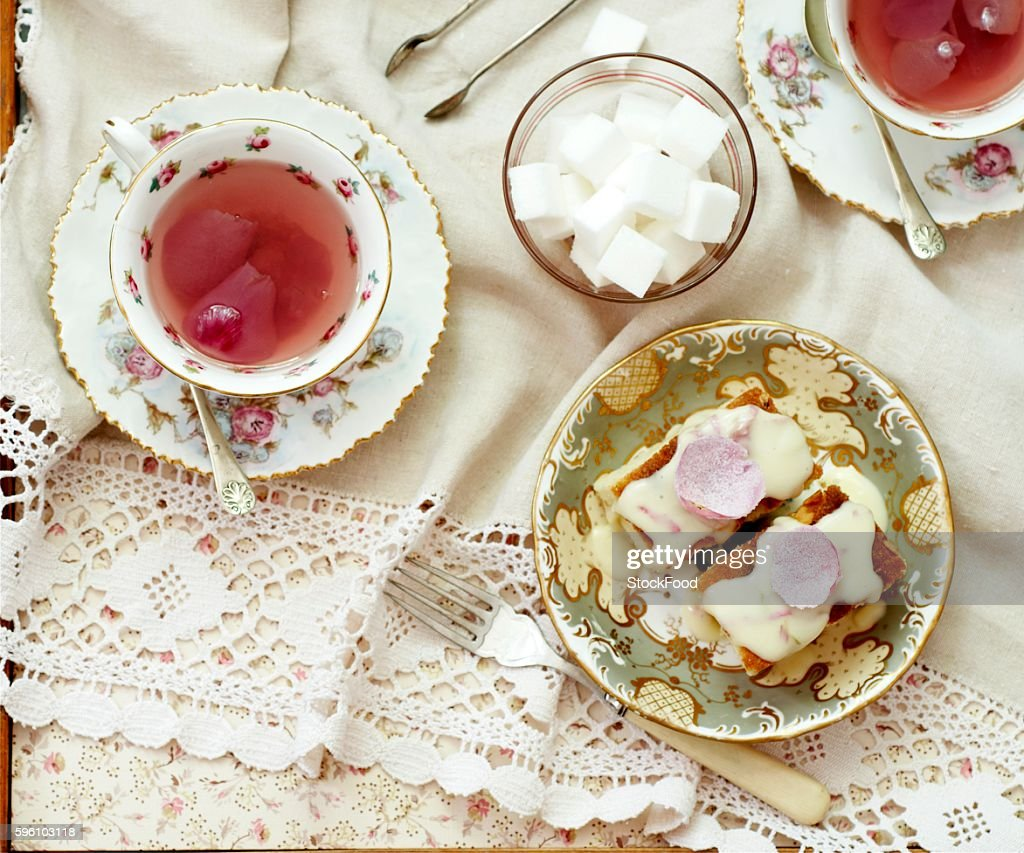 Almond cakes topped with rose petals and sugar icing, with rose tea and sugar cubes
