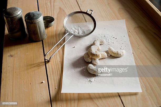 Almond cookies on paper sprinkled with icing sugar