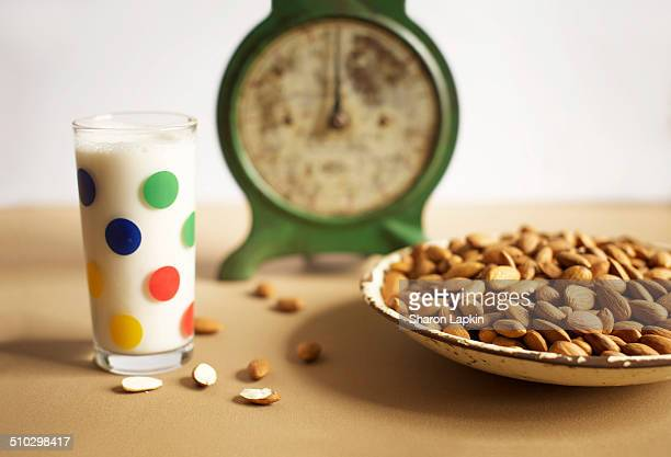 Almond milk in glass with nuts and kitchen scales