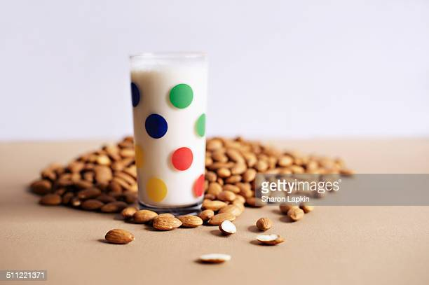 Almond milk in glass with raw almonds