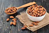 White ceramic bowl with a spoon full of almonds on a wooden table