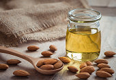 Almond oil in glass bottle and almonds on wooden table