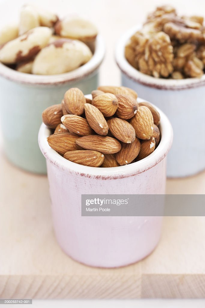 Almonds, walnuts and brazilian nuts in containers, close-up : Stock-Foto