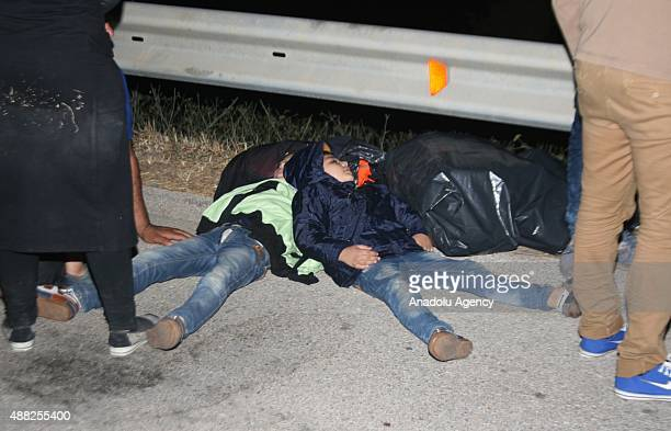 Almost 100 refugees wait to taken to the police department after they were crashed to police car as they prepare to pass through another country in...
